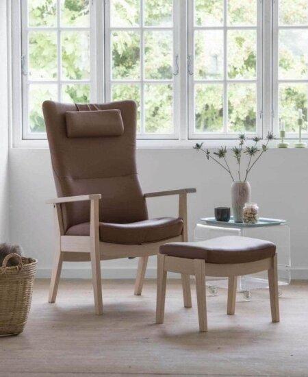 Edge 7910, lænestol i caramel farvet læder, med tilhørende skammel i lyse omgivelser