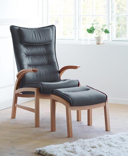 Cantate 6010, sort læder lænestol med egetræsstel i lyst miljø