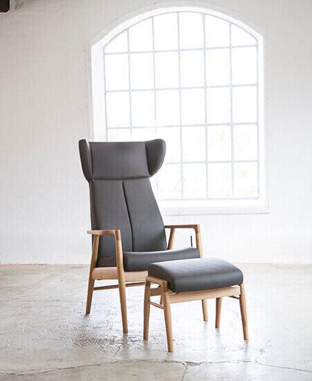 Nobel 8920 lænestol med øreklapper. Stolen er polstreret med brun læder og har egetræsstel. Matchende Nobel fodskammel
