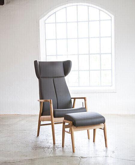 Nobel 8920, brun læder lænestol med egetræsstel, øre og tilhørende skammel i lyst miljø