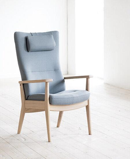 Plus 5910, lys grå lænestol med egetræs stel i lyst miljø