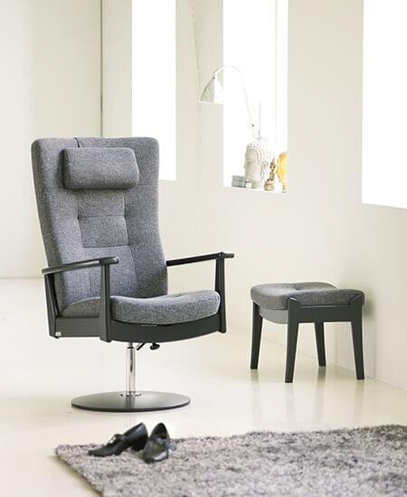 Plus 5980, grå lænestol med drejefod og fodskammel i lyst miljø